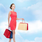 Smiling elegant woman in dress with shopping bags — Foto de Stock