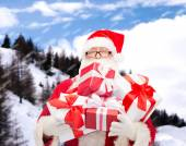 Man in costume of santa claus with gift boxes — Stockfoto