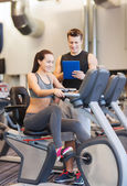 Happy woman with trainer on exercise bike in gym — Foto de Stock