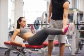 Woman with trainer doing abdominal exercise in gym — Stock fotografie