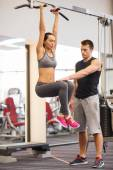 Young woman with trainer doing leg raises in gym — Stock fotografie
