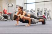 Smiling couple doing push-ups in the gym — Stock Photo