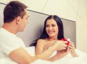 Man giving woman little red gift box — Stock Photo