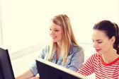 Two smiling girls in computer class — Foto de Stock