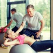 Smiling young woman with personal trainer in gym — Stock Photo #60478311
