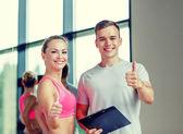 Mujer joven sonriente con entrenador personal en gimnasio — Foto de Stock