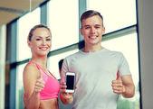Χαμογελώντας νεαρή γυναίκα με προσωπικό γυμναστή στο γυμναστήριο — Stockfoto