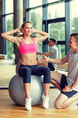 Smiling man and woman with exercise ball in gym — Stock Photo