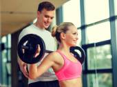 Smiling man and woman with barbell in gym — Foto de Stock