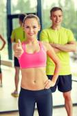 Sonriendo el hombre y la mujer mostrando los pulgares para arriba en gimnasio — Foto de Stock