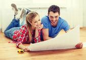 Sonriente pareja mirando plano en casa — Foto de Stock