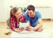 Couple souriant en regardant tablet pc à la maison — Photo