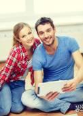 Sonriente pareja mirando tablet pc en casa — Foto de Stock