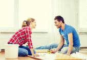 Smiling couple measuring wallpaper — Stock Photo