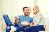 Smiling couple with popcorn choosing what to watch — Foto de Stock