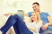 улыбается счастливая пара с планшетного пк на дому — Стоковое фото