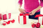 закройтесь женщины, украшающей рождественские подарки — Стоковое фото