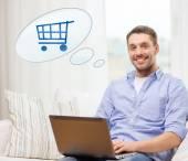 Uomo sorridente con il computer portatile lo shopping online a casa — Foto Stock