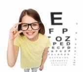Smiling little girl in eyeglasses with eye chart — 图库照片