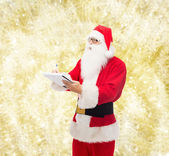 Man in costume of santa claus with notepad — Photo