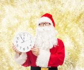 Mann im Kostüm des Weihnachtsmannes mit Uhr — Stockfoto