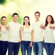 Smiling teenagers in t-shirts showing thumbs up — Foto de Stock   #60563817