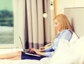 Feliz empresaria con el portátil en la habitación del hotel — Foto de Stock
