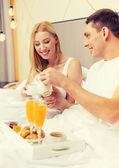 Smiling couple having breakfast in bed in hotel — Foto de Stock