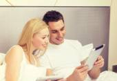 Smiling couple in bed with tablet pc computers — Foto de Stock