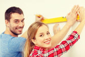 Couple building using spirit level to measure — Stock Photo