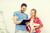 Lachende paar met klembord en behang roll — Stockfoto