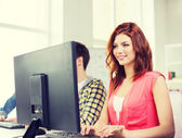Smiling female student in computer class — Stock Photo