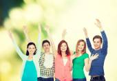 Group of smiling students waving hands — Stock Photo