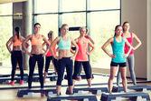 Grupp kvinnor som arbetar med steppers i gym — Stockfoto