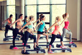 Group of women with dumbbells and steppers — Stock Photo