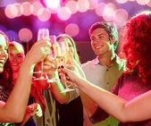 Улыбающиеся друзья со стаканами шампанского в клубе — Стоковое фото