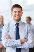 Smiling businessman with colleagues in office — Stock Photo