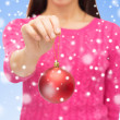 Close up of woman in sweater with christmas ball — Stock Photo #60622525