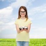 Smiling cute little girl in black eyeglasses — Stock Photo #60624189