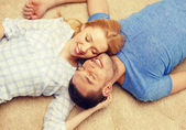 Smiling happy couple lying on floor at home — 图库照片