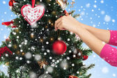 Close up of hands with christmas tree decoration — Foto Stock