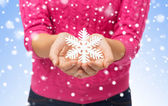 Close up of woman in sweater holding snowflake — Foto de Stock