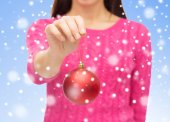 Close up of woman in sweater with christmas ball — 图库照片