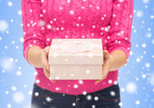 Close up of woman in pink sweater holding gift box — 图库照片