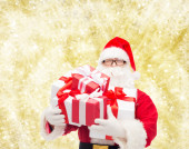 Man in costume of santa claus with gift boxes — Foto Stock