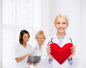 Smiling female doctor with heart and stethoscope — 图库照片