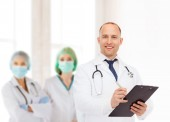 Smiling male doctor with clipboard and stethoscope — ストック写真