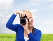 Femme souriante prendre photo avec appareil photo numérique — Photo