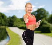Улыбается спортивный женщина с смартфона — Стоковое фото
