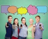 Happy friends showing blank smartphones screens — Stock Photo